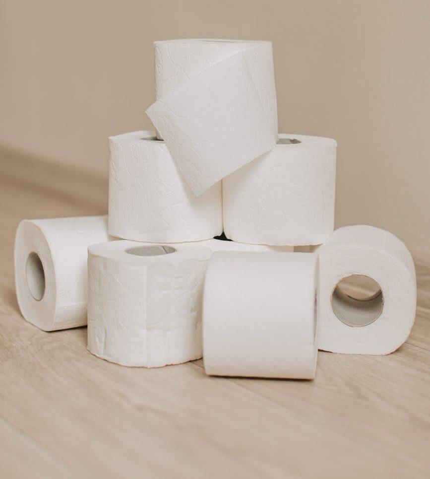 tubes of white toilet paper on bathroom floor